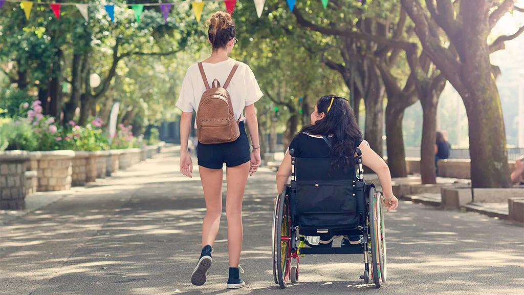 Dos mujeres jóvenes,una en silla de ruedas, paseando por un parque