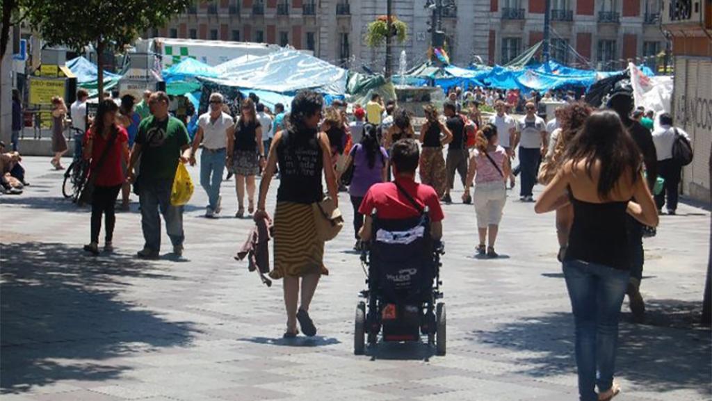 Hombre en silla de ruedas en medio de una calle concurrida