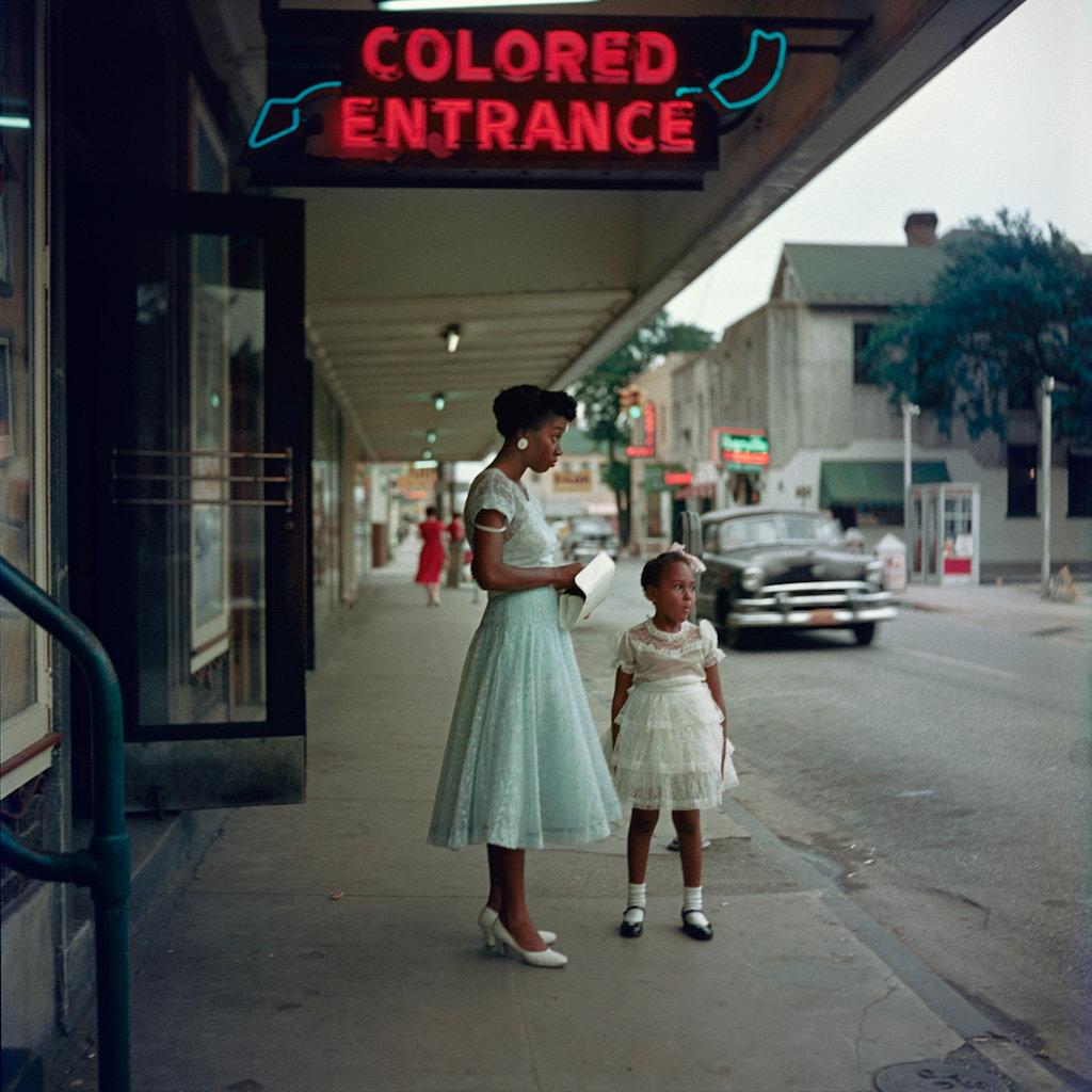 Dos mujeres negras bajo un cartel que indica entrada para negros