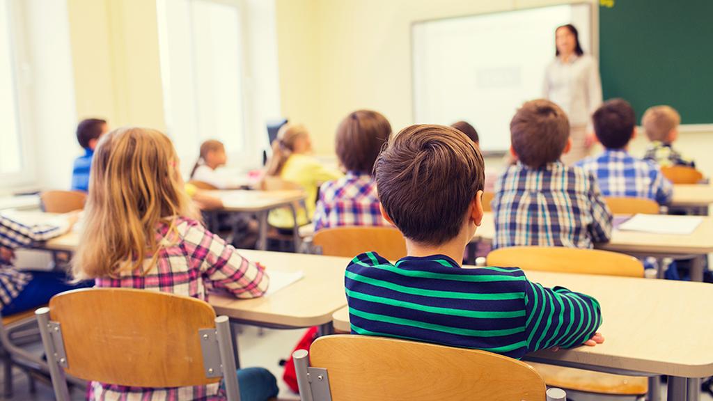 Alumnado de primaria y su profesora en un aula