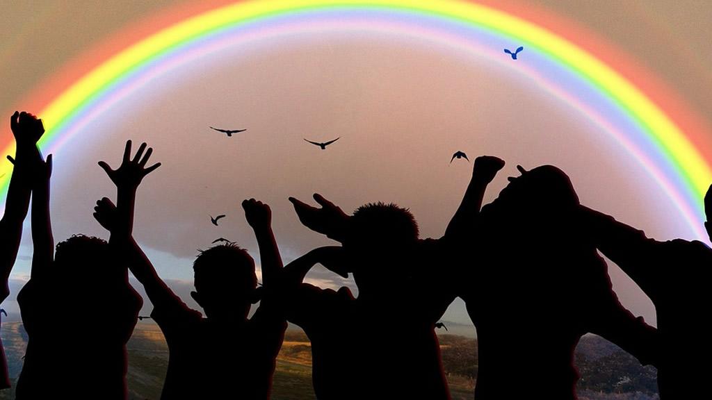 Siluetas de niños de espaldas mirando hacia el arcoiris