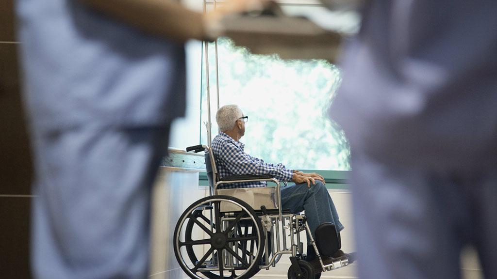Dos personas sanitarias y hombre en silla de ruedas al fondo de una sala