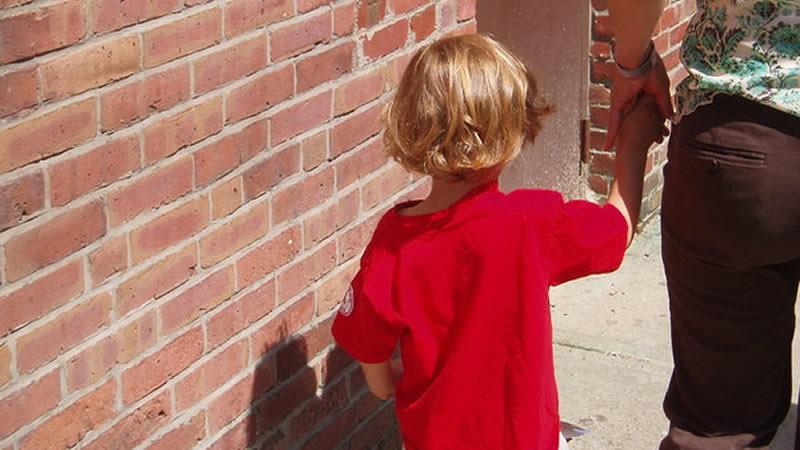 Niño paseando de la mano del adulto